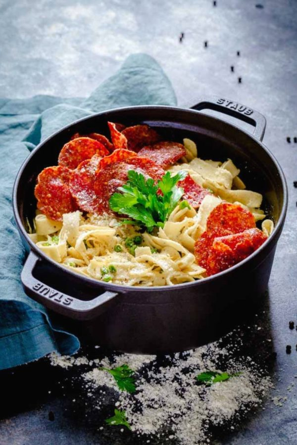 Lemon Pasta with Crispy Salami in a black Staub cocotte on a rustic table.