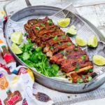 Rack of BBQ ribs on a silver serving platter surrounded by cilantro and limes.
