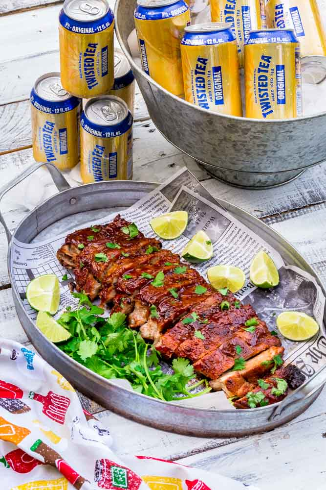 Cans of beer next to a platter of cooked, sliced and garnished baby back ribs.