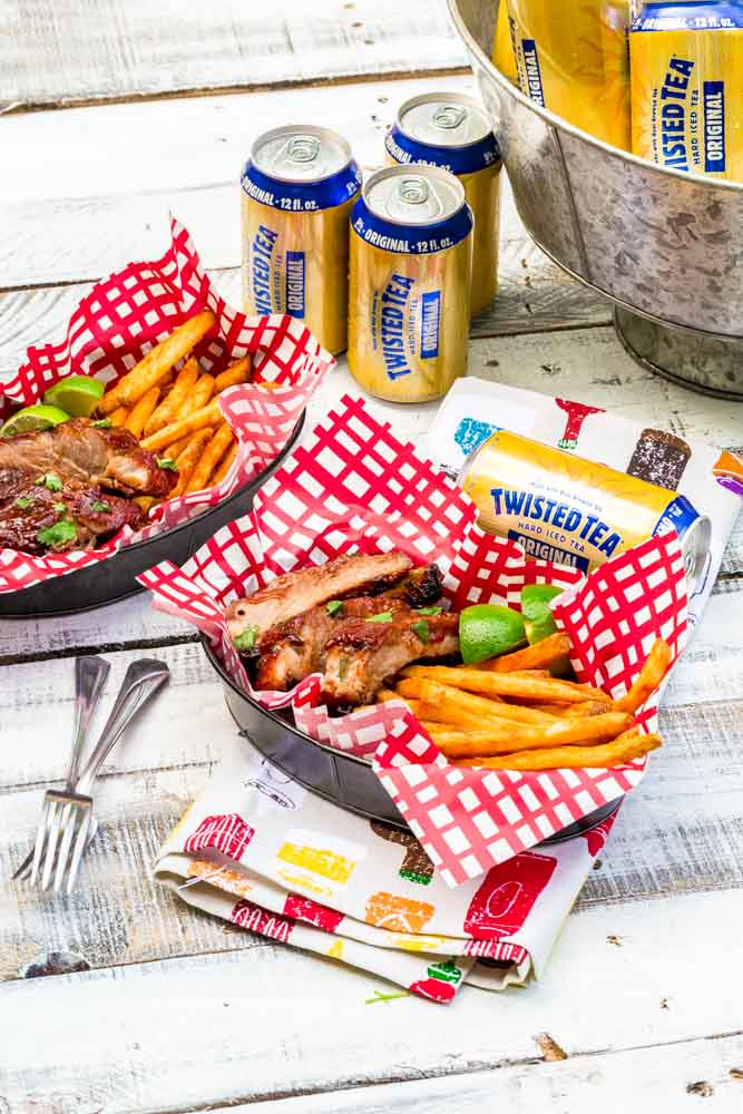 Baby back ribs, fries and lime slices in a food basket with a red-checkered liner.