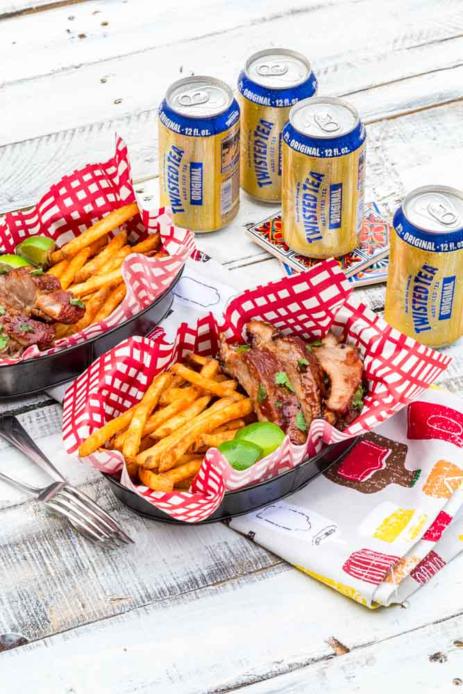 White picnic table setting with single serve food baskets filled with BBQ ribs and French fries.