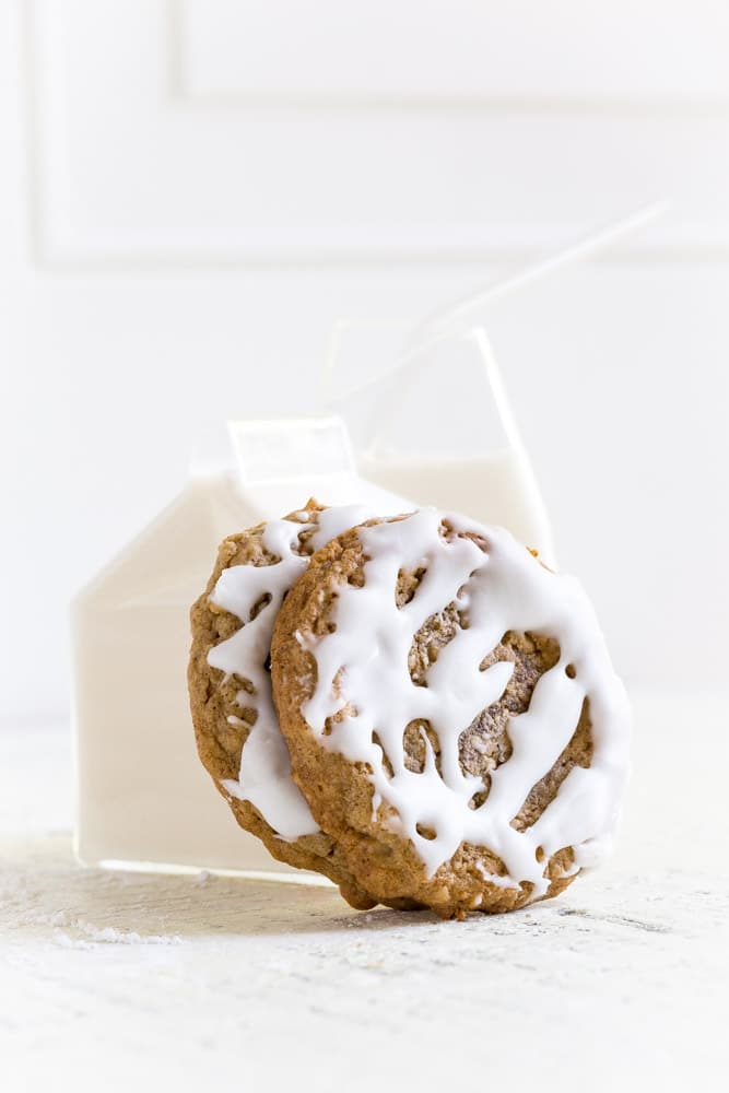 Two oatmeal cookies leaning up against a individual-sized glass carton of milk with glass straw.