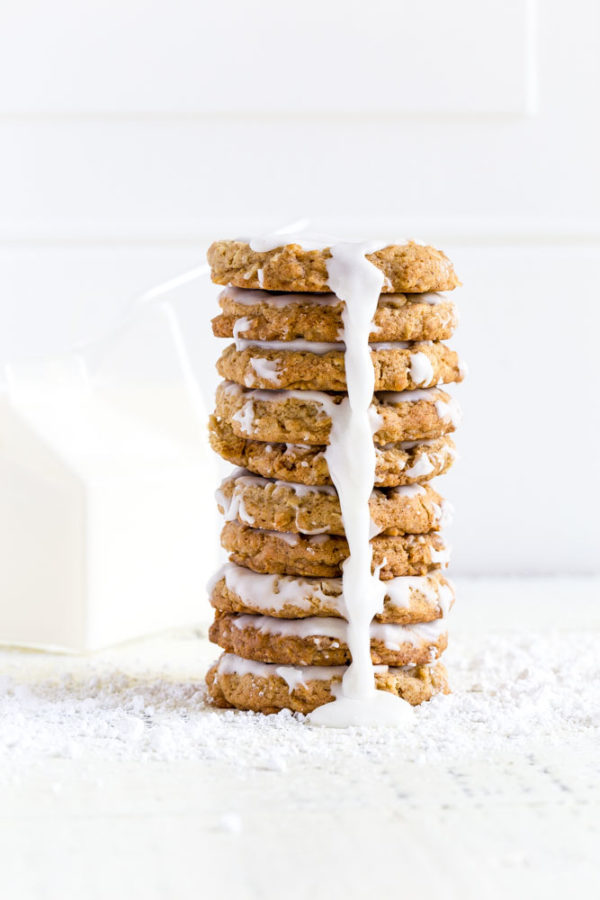 A stack of iced oatmeal cookies with a glass carton of milk and straw.