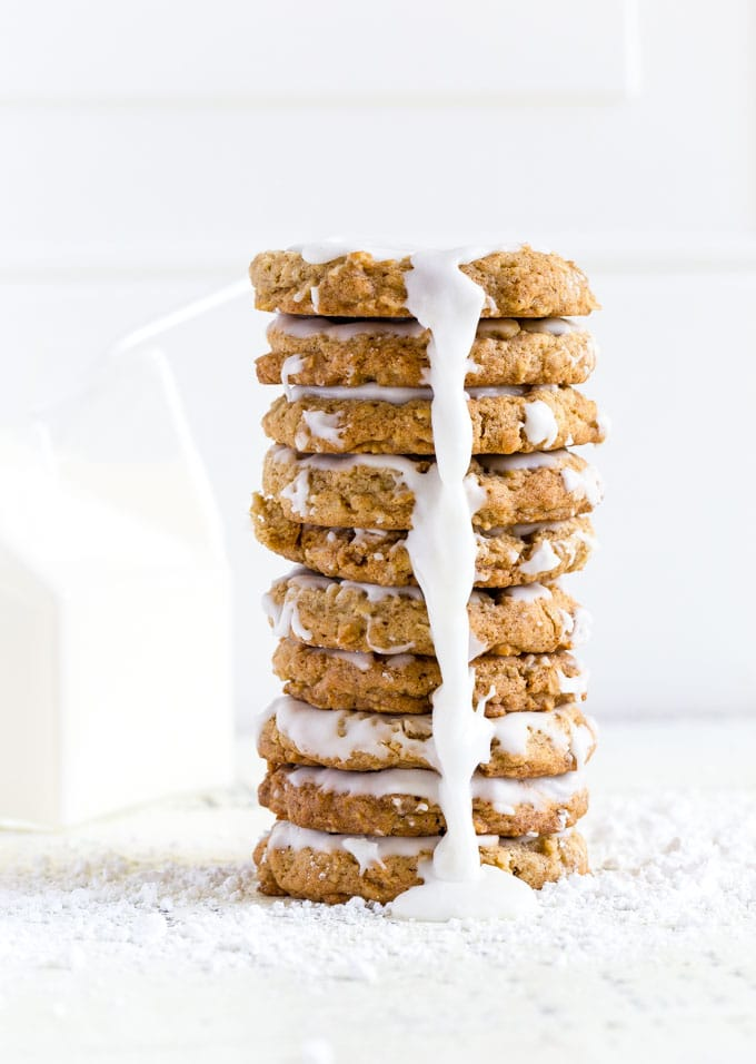A delicious stack of 9 oatmeal cookies with frosting drizzling down the front.
