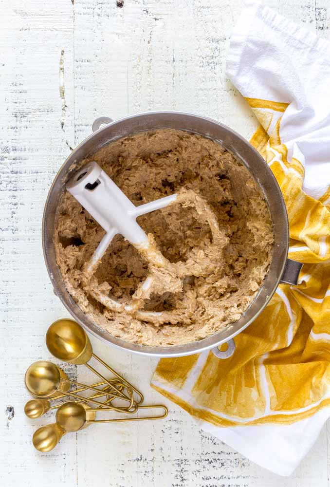 Oatmeal cookie dough in a stainless steel mixing bowl with a white flat beater attachment.