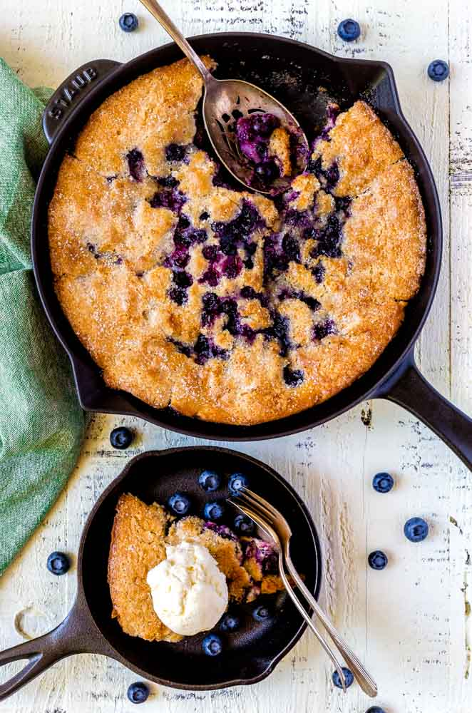 A black Staub cast-iron skillet with blueberry cobbler and a large metal serving spoon.
