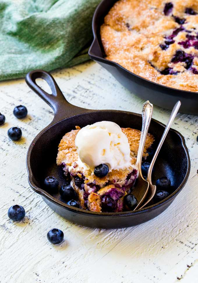 A single portion of blueberry cobbler topped with a large scoop of vanilla ice cream.