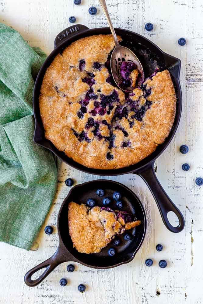 Blueberry cobbler served in a Staub cast-iron skillet with an antique metal serving spoon.