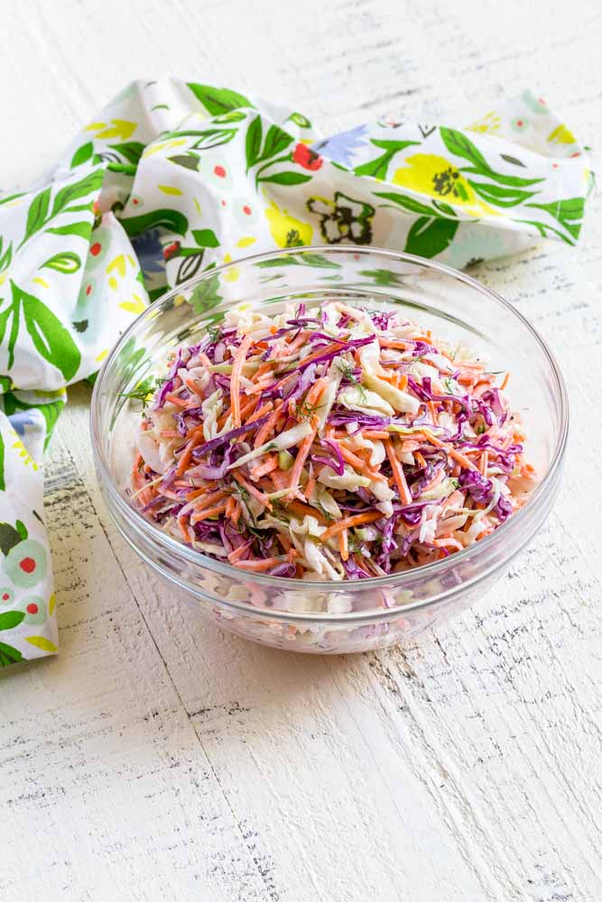 Coleslaw dressing mixed into shredded cabbage for coleslaw recipe.