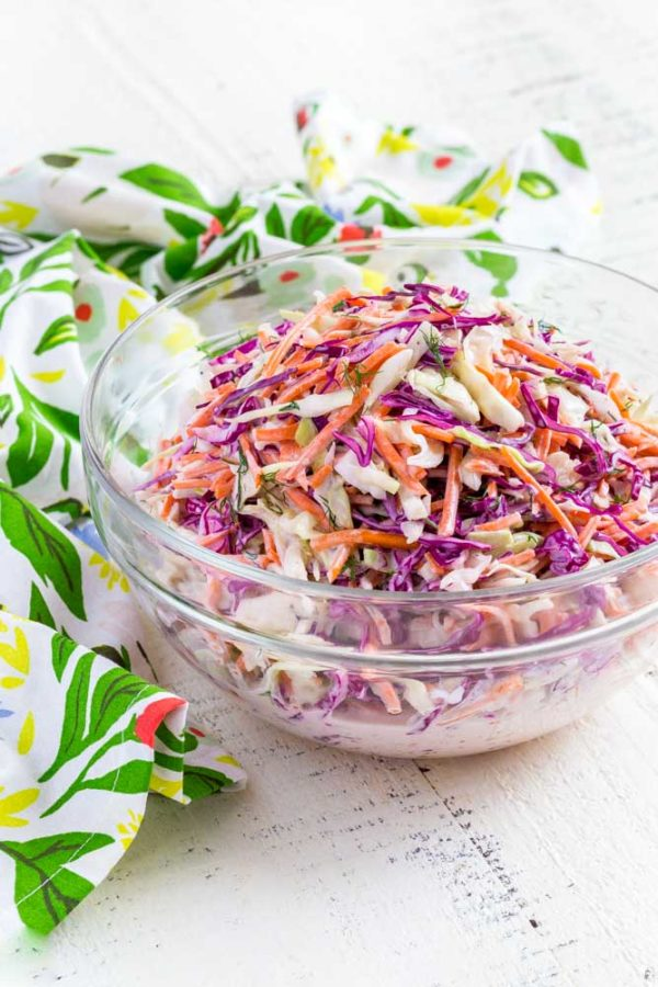 A clear bowl filled with colorful coleslaw next to a flour sack towel on a white farm table.