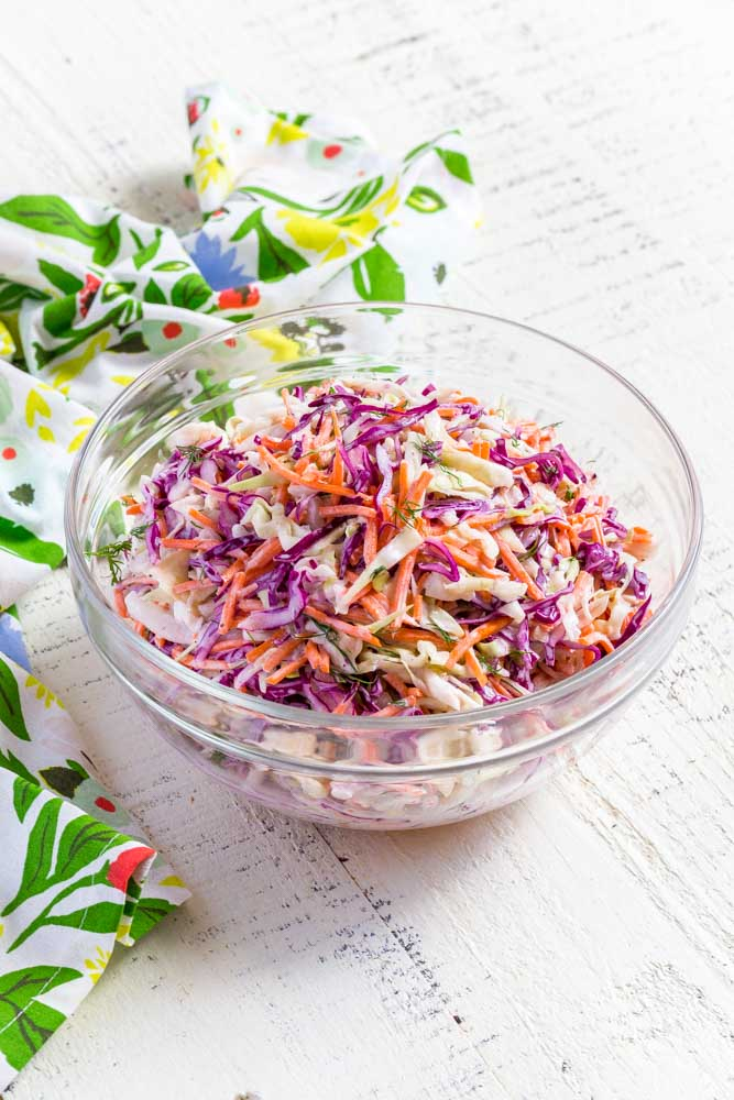 Coleslaw in a clear glass serving bowl on a white farmhouse table.