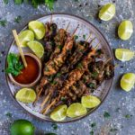 Grilled Pork Loin on wooden skewers next to parsley and wedges of lime.