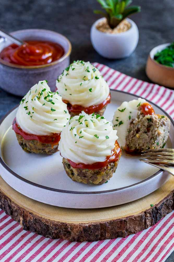 Mini Meatloaf on a white serving platter next to a small bowl of ketchup and a bowl of chopped parsley.