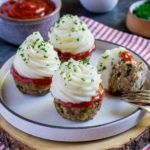 Four meatloaf cupcakes on a small round serving dish next to a dish of ketchup.