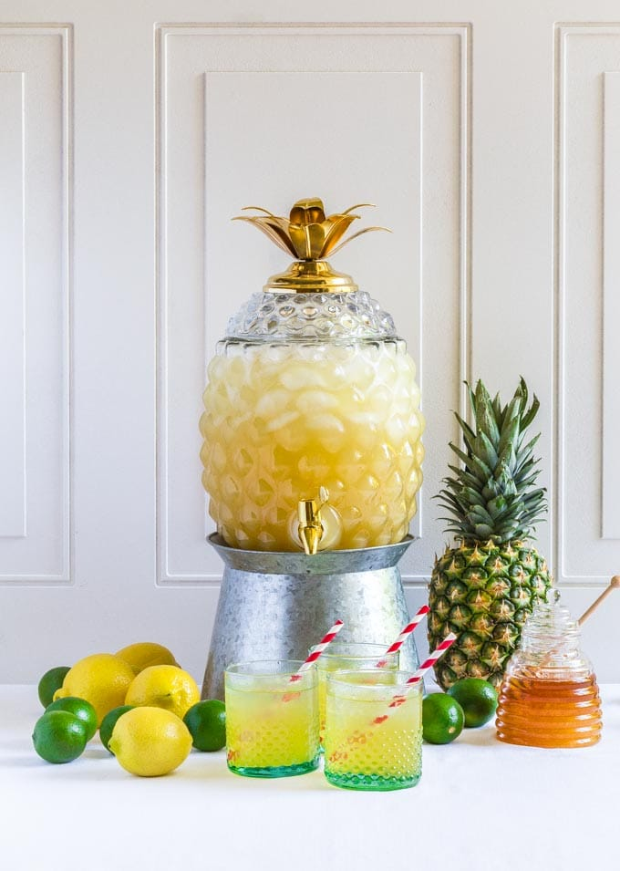 Pineapple Party Punch served in a glass pineapple container on a metal stand.