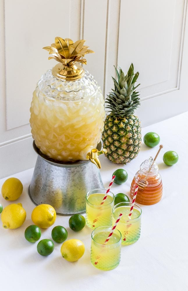 A glass pineapple beverage dispenser with a golden crown filled fruit punch.