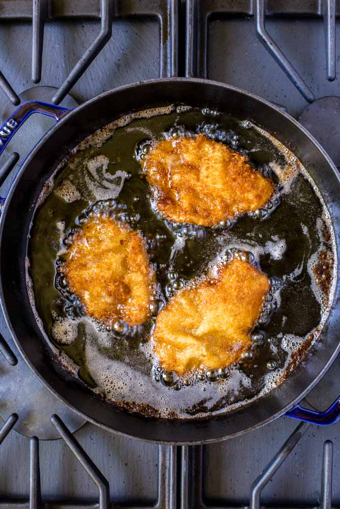 Three pieces of schnitzel being fried on the stovetop in a Staub universal pan.