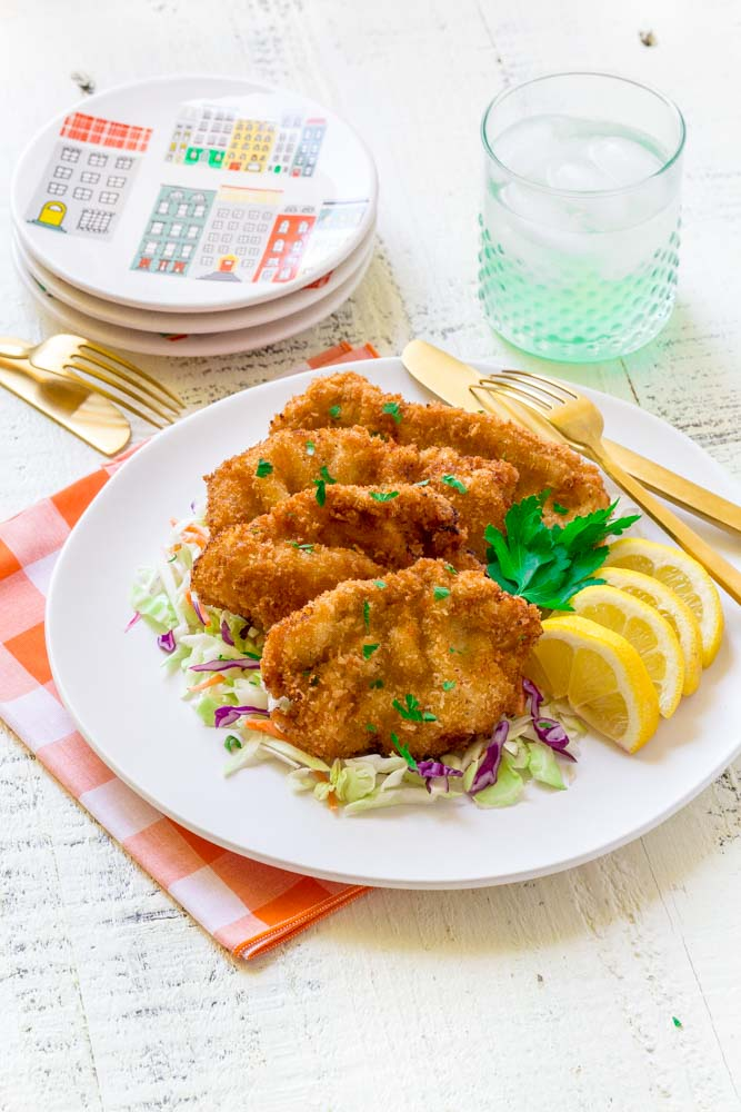 Four pieces of schnitzel sprinkled with parsley on a white serving plate with lemon wedges.