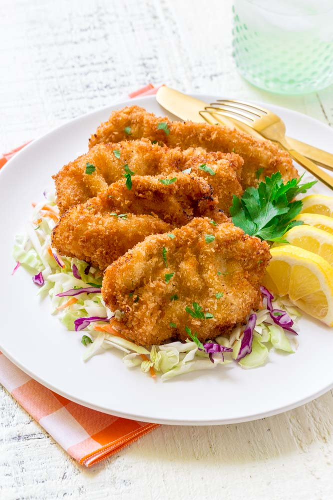Four pieces of wiener schnitzel on a white serving dish with garnishes of parsley and lemon.