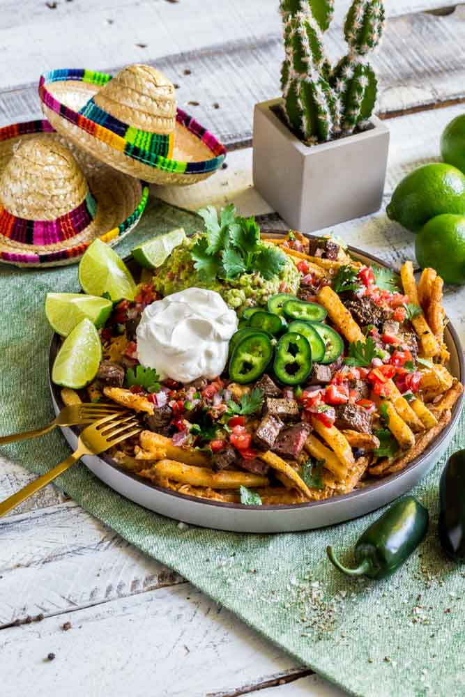 Carne asada fries on a serving platter with Mexican garnishes.