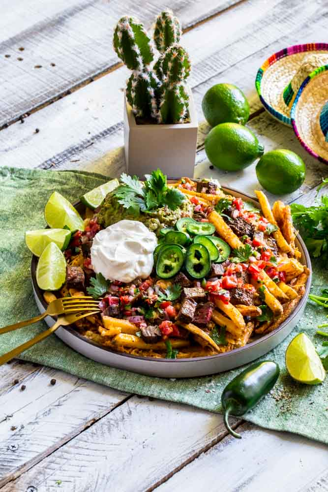 Beautifully plated carne asada fries loaded up with all the fixings and garnishes!