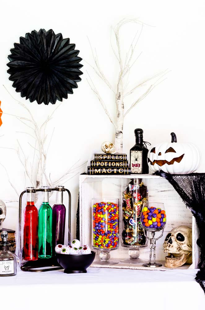 A Halloween table with jars of colorful candies.