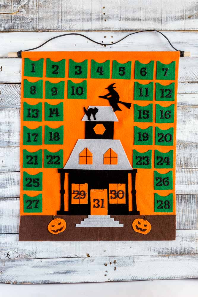 Halloween Calendar hung on a rustic white wall.