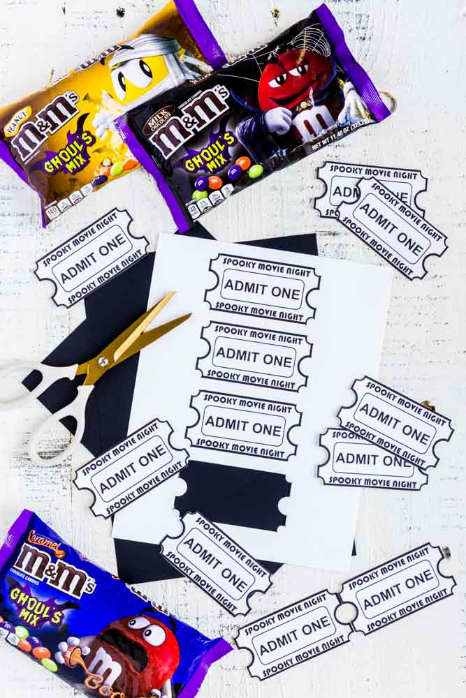 Printable movie night tickets, black paper and gold-and-white scissors on a white table.