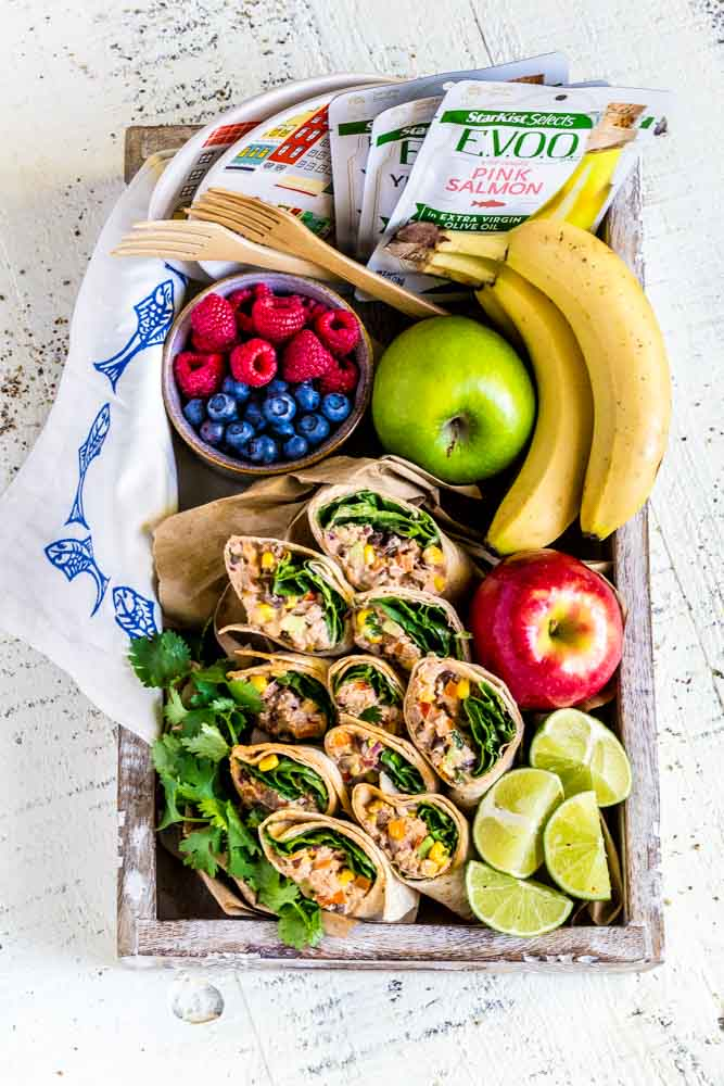 Wraps with chipotle mayo served on a wooden tray with a variety of fresh fruit.