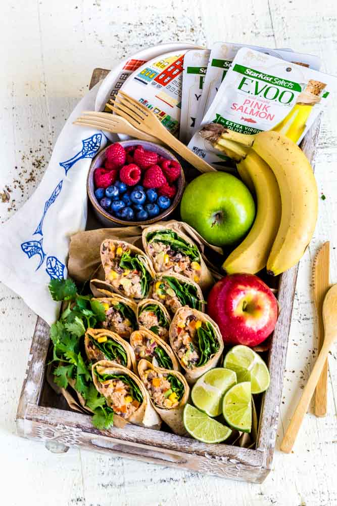 A serving tray filled with healthy wraps with chipotle mayo, lime slices and fresh fruit.