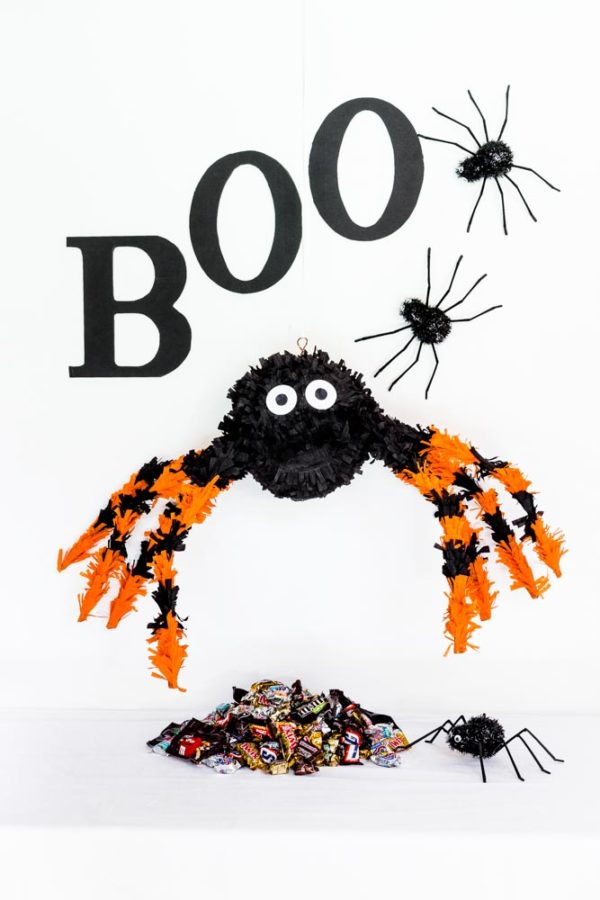 DIY Spider Pinata hanging above a pile of Halloween candy.