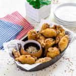 Crispy air fryer chicken wings in a serving basket with dipping sauce.