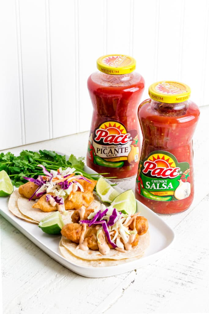 Recipe ingredients for fish tacos on a white rustic table with Mexican salsa.