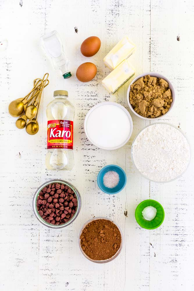 Ingredients for making chewy chocolate cookies laid out on a rustic white table.