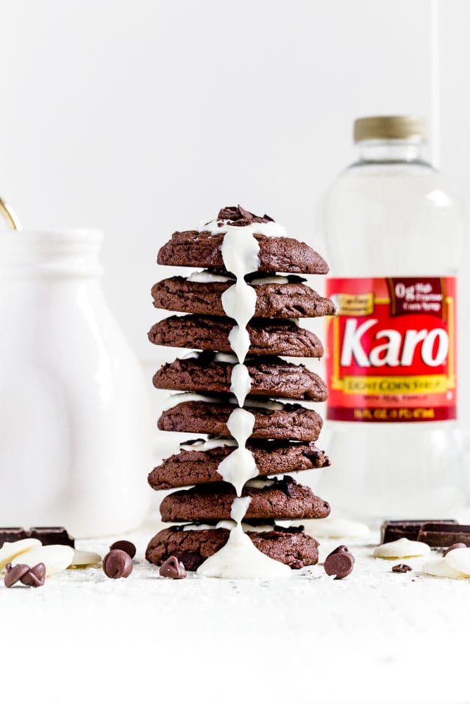 A stack of 8 triple chocolate cookies with white chocolate drizzled down the front.