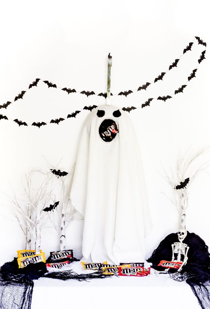 A DIY Halloween door hanger in the shape of a white ghost.
