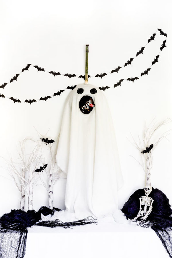 Halloween ghost flying among bats over white treetops.