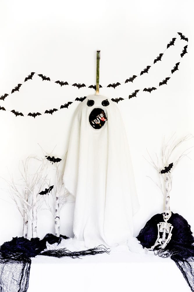A DIY Halloween ghost flying among bats over white treetops.