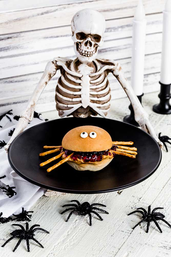 PB and J Spiders served on a black serving tray held by a Halloween skeleton.