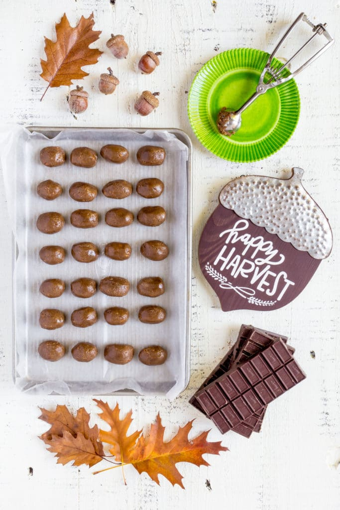 Oreo truffles shaped like acorns on a wax paper-lined baking tray.