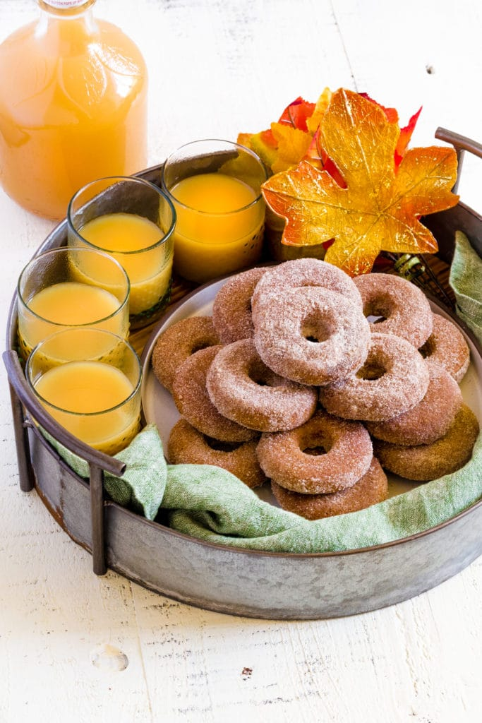One dozen apple cider donuts served on a rustic metal tray.