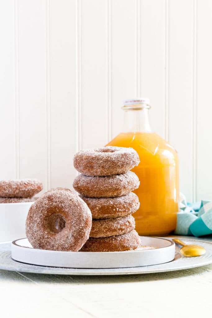 Five apple cider donuts stacked vertically on a tray with one donut leaning against the stack.