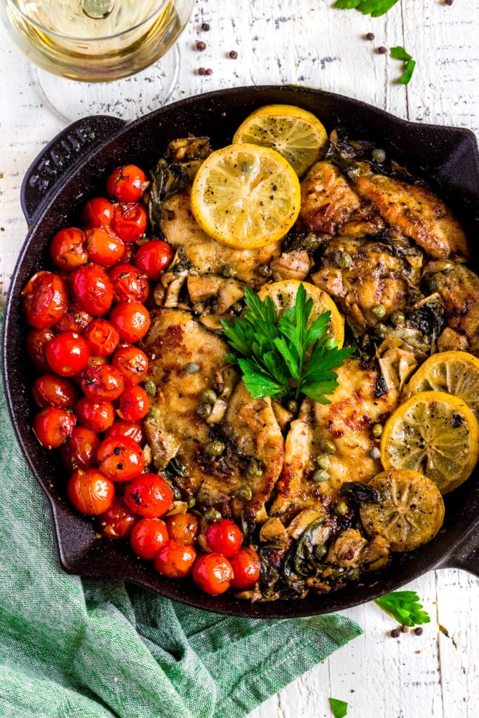 Lemon Chicken Piccata served in a cast-iron pan next to a glass of white wine.