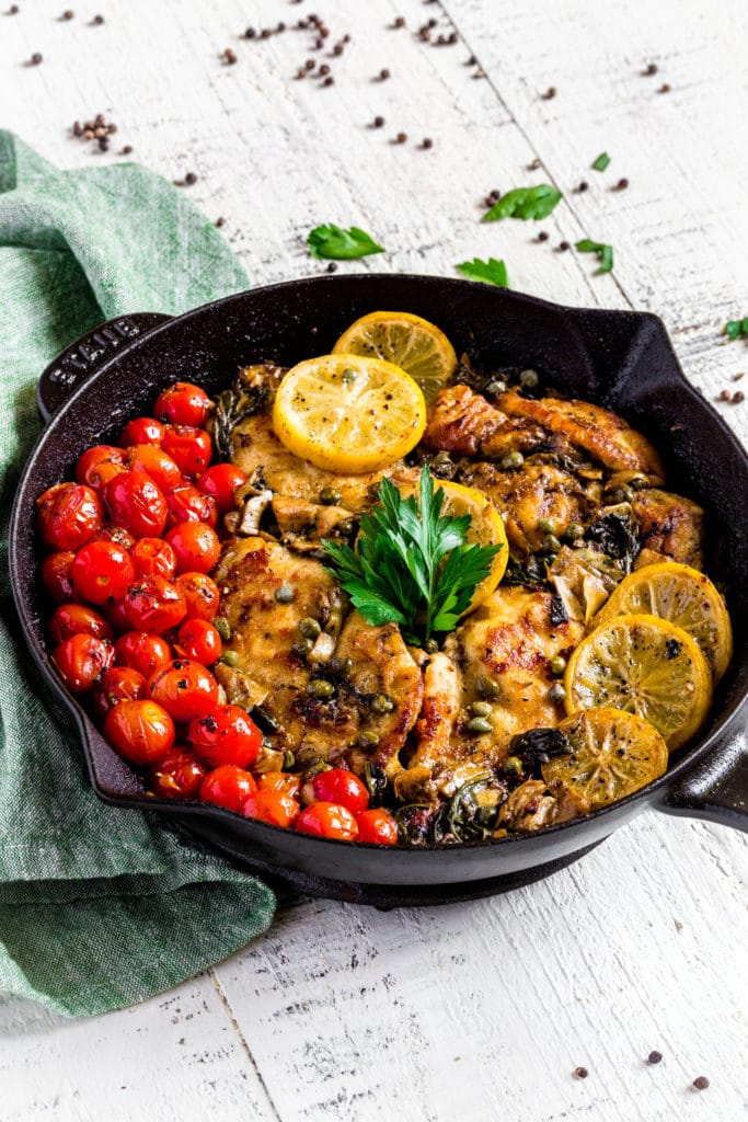 Lemon Chicken Piccata garnished with roasted cherry tomatoes, lemon slices and Italian parsley.