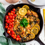Chicken piccata with lemon and capers in a skillet next to dinner plates and forks.