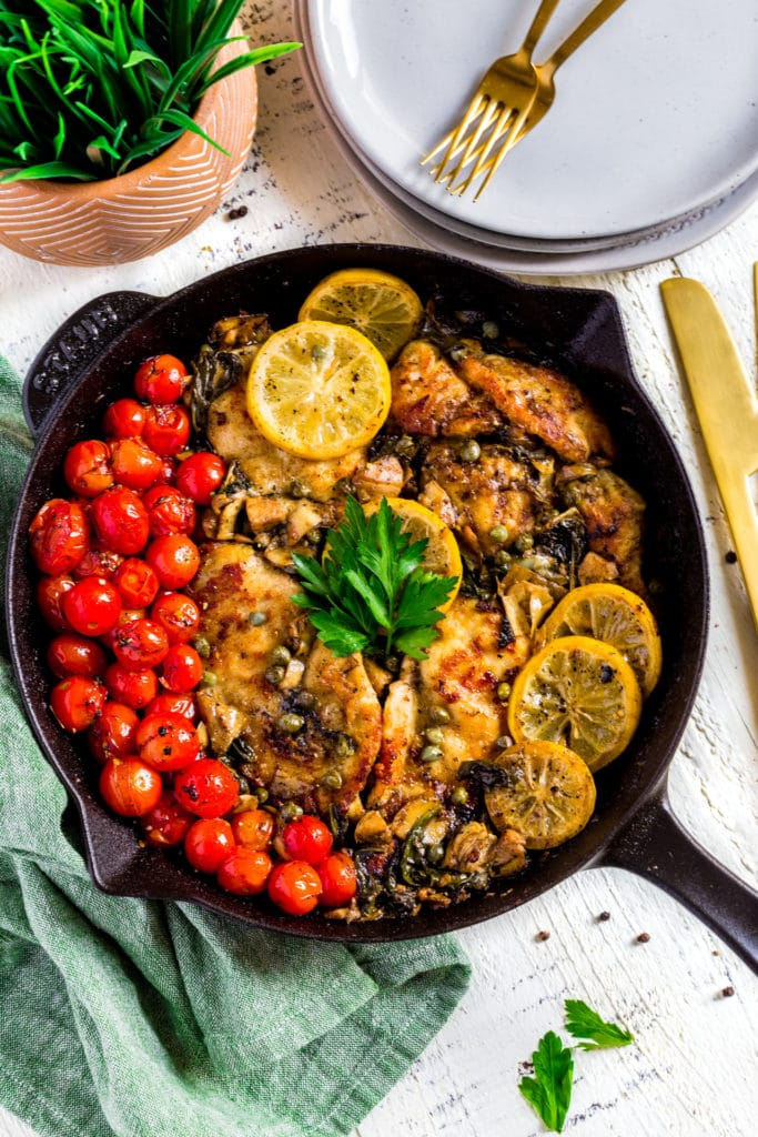 Healthy Chicken Piccata with lemon, tomatoes, artichokes and spinach served in a black cast-iron skillet.
