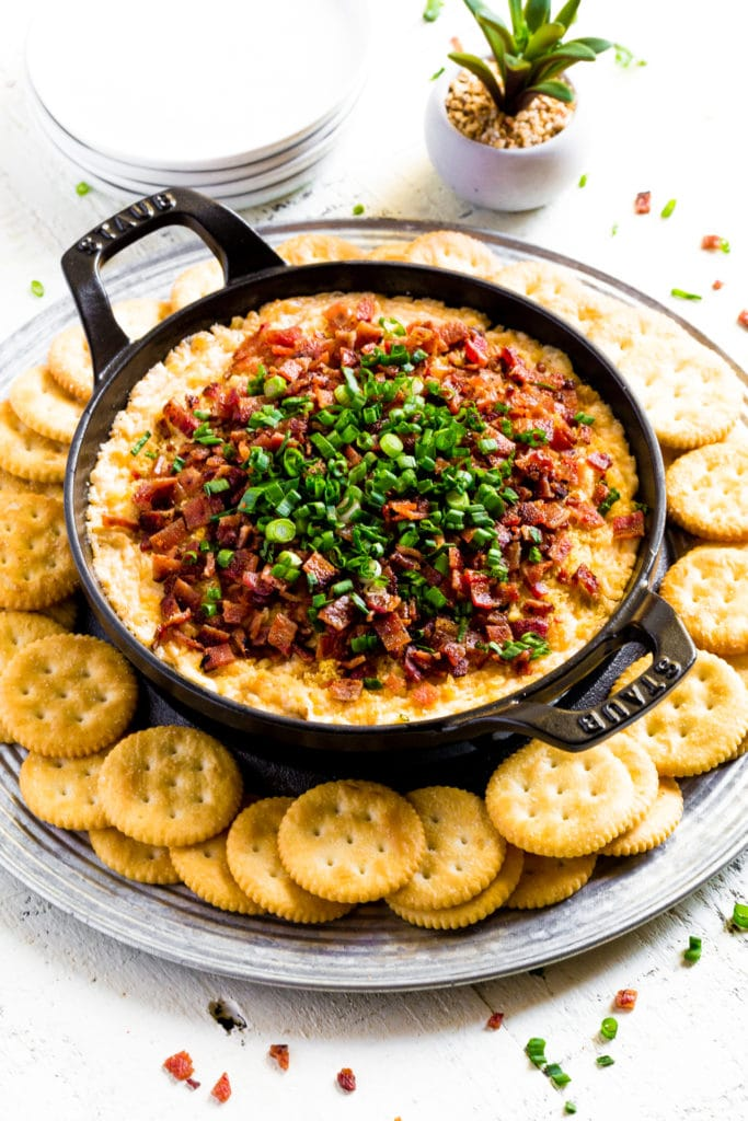 Cheese dip served in a round cast-iron baking dish surrounded by crackers.