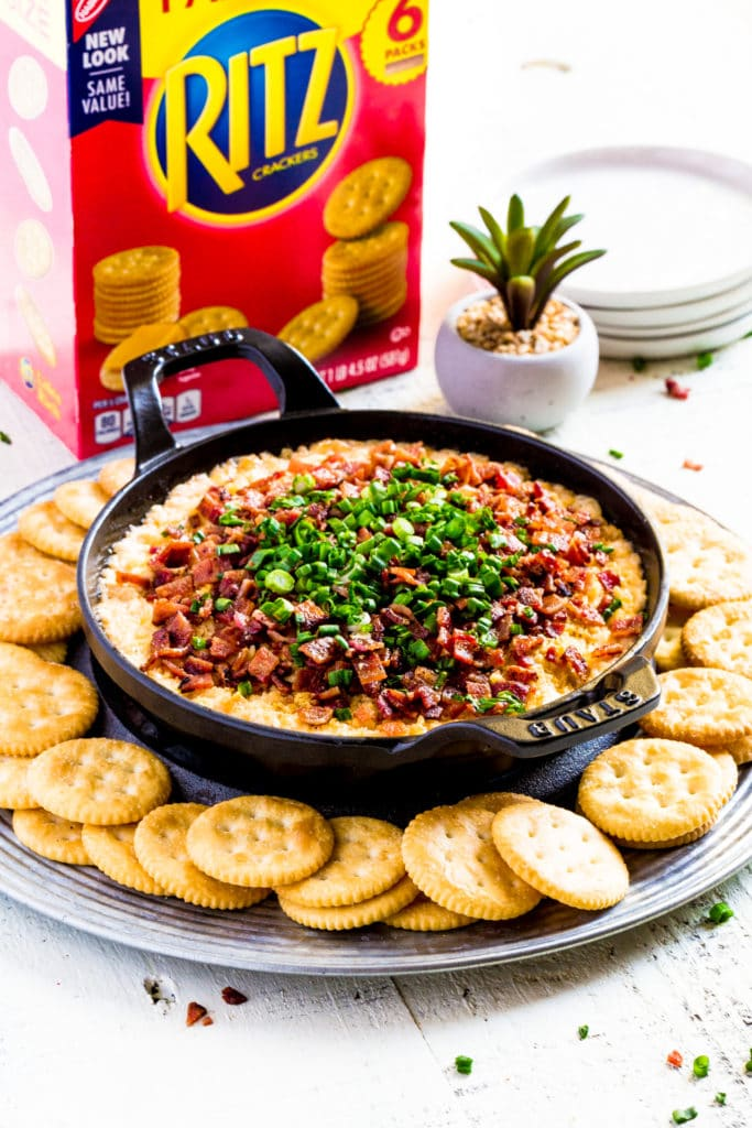 Loaded cream cheese dip garnished with bacon and green onions, served with butter crackers.