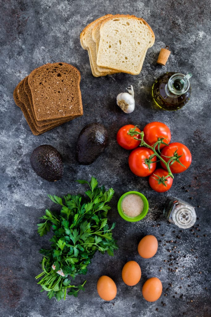 Ingredients for making avocado toast with charred tomatoes and eggs.