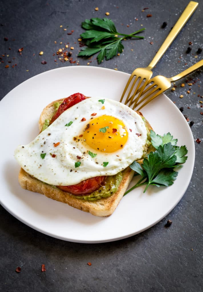 Garlic toast topped with avocado, charred tomatoes and egg.
